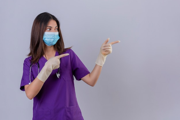 若い女性看護師が医療の制服保護マスクの手袋を着用し、聴診器を両手と横に指で指している