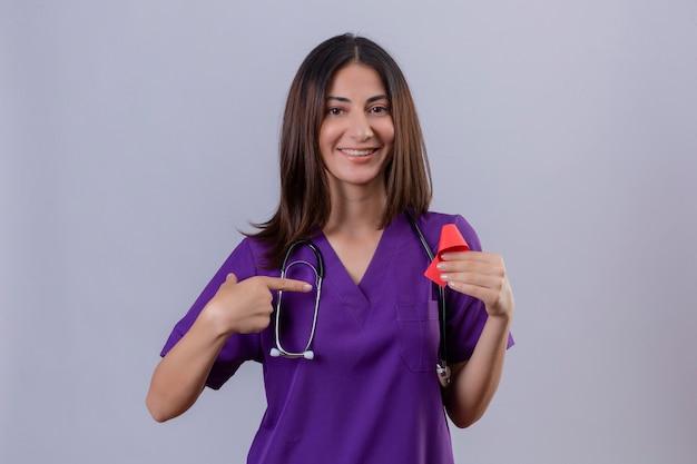 Молодая медсестра в униформе со стетоскопом держит красную ленту, символ борьбы со спидом, указывая на нее с дружелюбной улыбкой указательным пальцем
