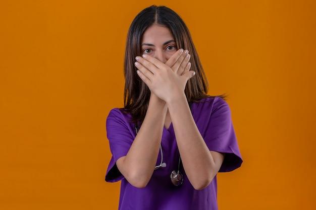 Infermiera della giovane donna che indossa l'uniforme e con lo stetoscopio scioccato che copre la bocca con le mani in piedi
