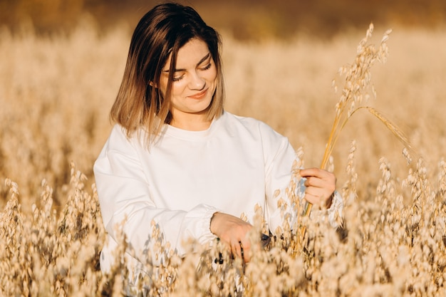 A young woman in an oat field