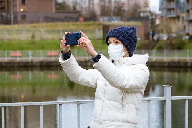 Молодая женщина кавказской национальности в теплой куртке в защитной маске фотографируется по телефону ...
