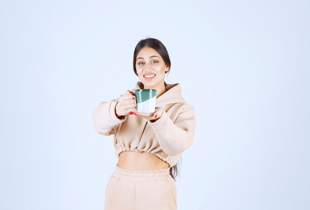 Young woman offering coffee in a green mug