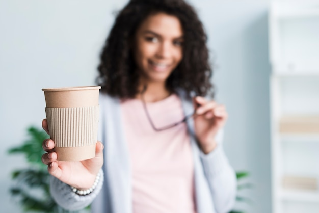 Young woman offering to drink coffee at work