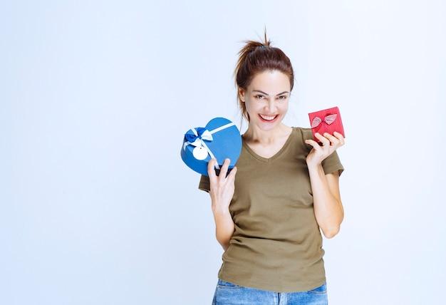 Giovane donna che offre scatole regalo rosse e blu a forma di cuore al suo partner