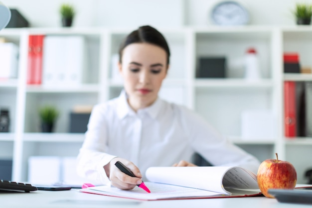 Young woman in the office with documents and a marker. a photograph of the depth of field, a highlighted focus on the document and the marker.