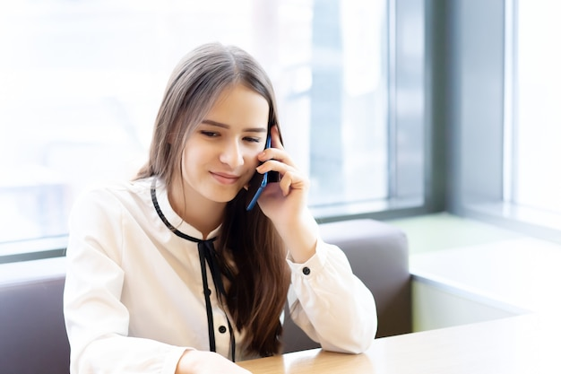 Молодая женщина офисный работник в кафе со смартфоном, разговаривает, улыбается