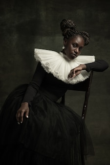 La giovane donna in vestito antiquato si siede su una sedia