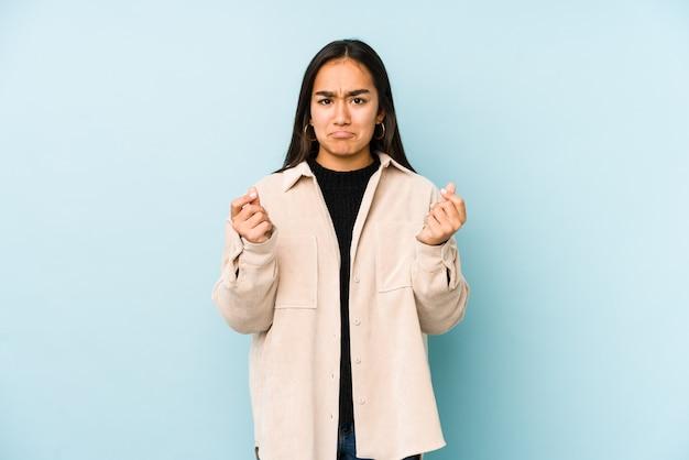 Молодая женщина на голубой стене показывает, что у нее нет денег.