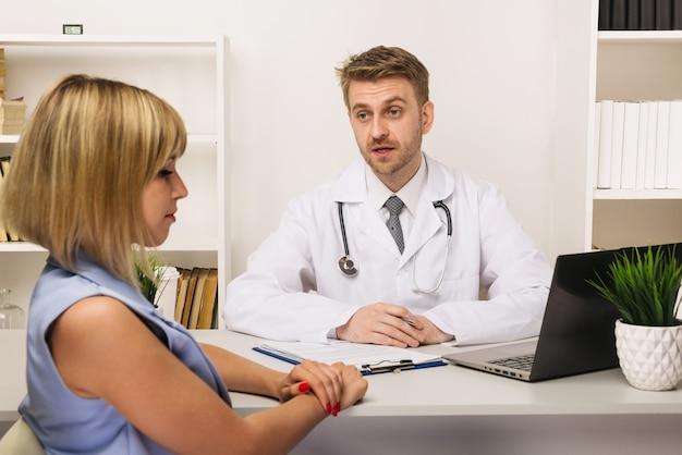 彼のオフィスで男性外科医またはセラピストと相談している若い女性。医師に選択的に焦点を当てます。