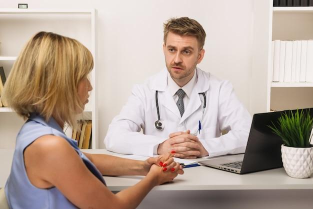 彼のオフィスで男性の外科医またはセラピストと相談している若い女性