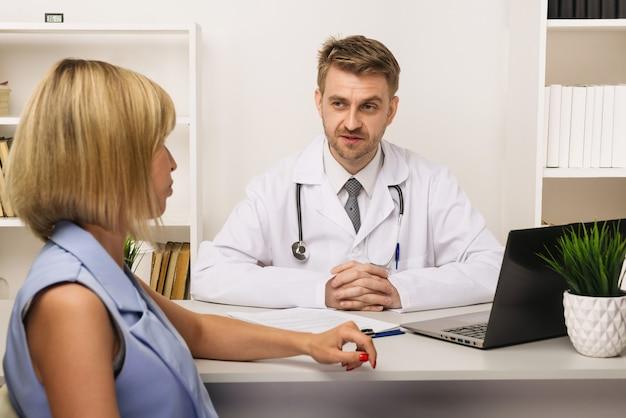 彼のオフィスで男性外科医またはセラピストと相談している若い女性