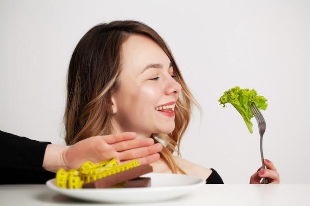 Молодая женщина на диете, ест только салат и пытается похудеть