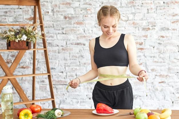 다이어트에 젊은 여자, 그녀는 부드러운 측정 테이프, 테이블에 신선한 야채로 허리를 측정