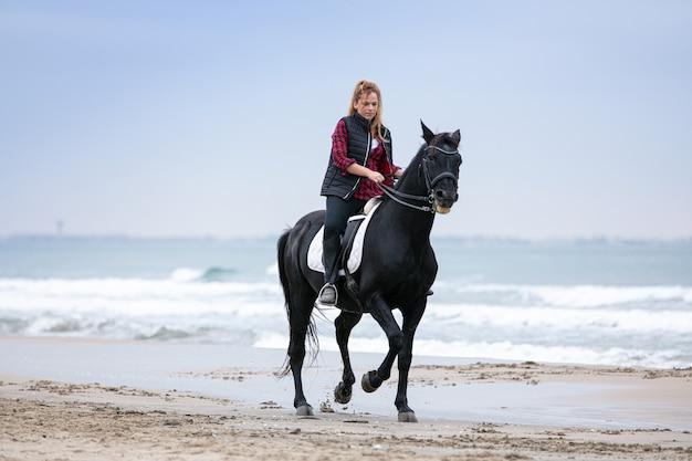 Молодая женщина на лошади на пляже в пасмурный день