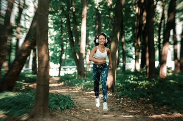숲 후면보기에서 조깅에 젊은 여자