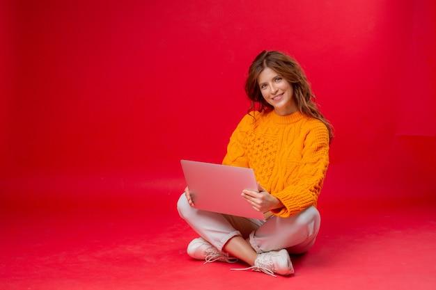 Молодая женщина на красном с ноутбуком сидит