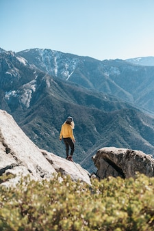 山の岩の上の若い女性