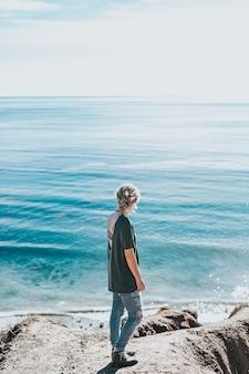 해안 근처 바위에 젊은 여자