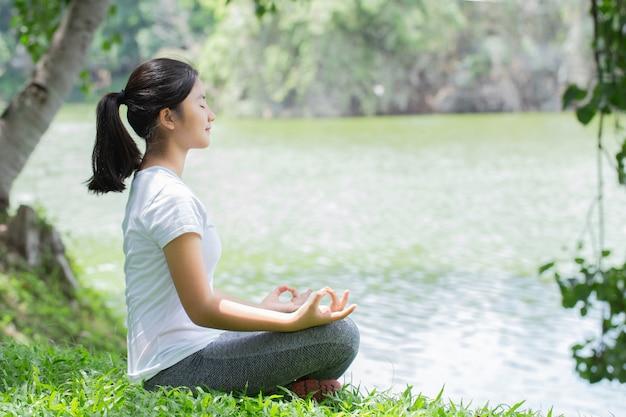 公園でリラックスするヨガマットの若い女性。自然の中でリラックス