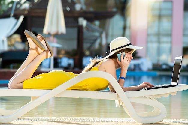 컴퓨터 노트북에서 작업 하 고 피서지에서 판매 전화에 대 한 얘기 수영장에서 비치의 자에 젊은 여자. 개념을 여행하는 동안 원격 작업 및 프리랜서 작업.