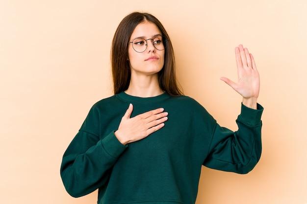 Молодая женщина на бежевом клятве, положив руку на грудь.