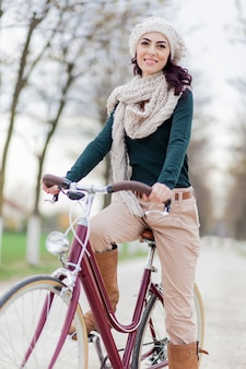 Молодая женщина на велосипеде зимой Premium Фотографии
