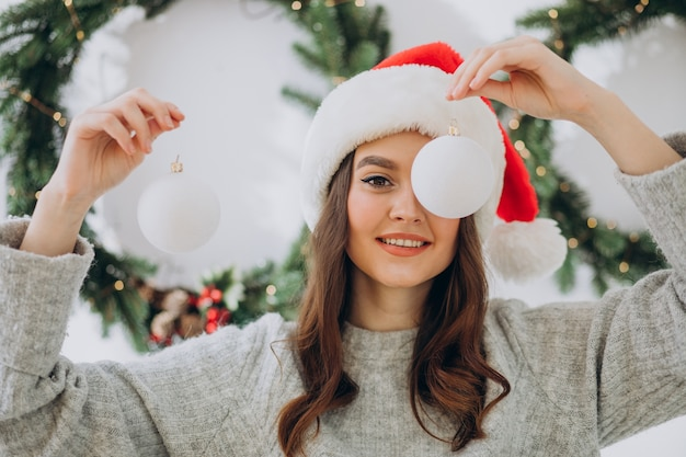 Молодая женщина на рождество с елочными игрушками