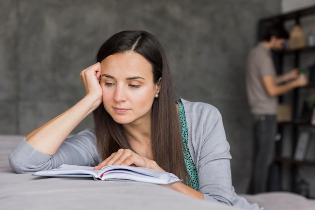 ソファの読書の若い女性