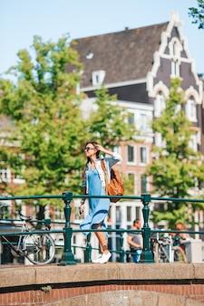 Молодая женщина на европейских каникулах в амстердаме у моста