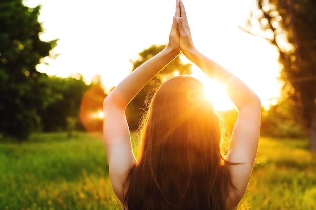 ヨガをしている日没の光の下でフィールド上の若い女性