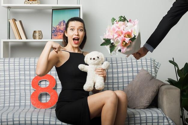 幸せな女性の日の若い女性がソファに座って、テディベアを指差して、リビングルームで男が花束を取ります