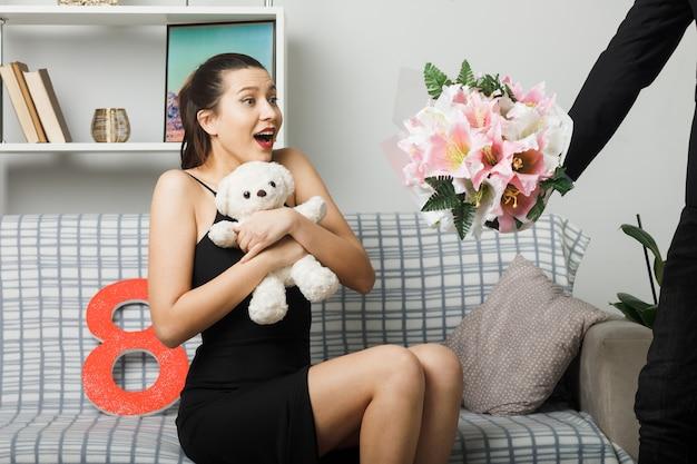 テディベアを保持しているソファに座って幸せな女性の日の若い女性は、リビングルームで男によって花束を取る