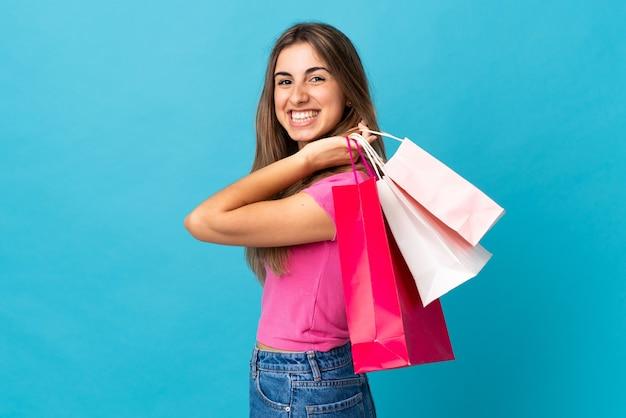 孤立した青い買い物袋を押しながら笑顔の若い女性