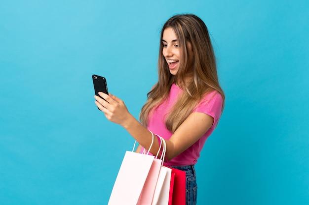 孤立した青い買い物袋を保持していると彼女の携帯電話で友人にメッセージを書くの若い女性