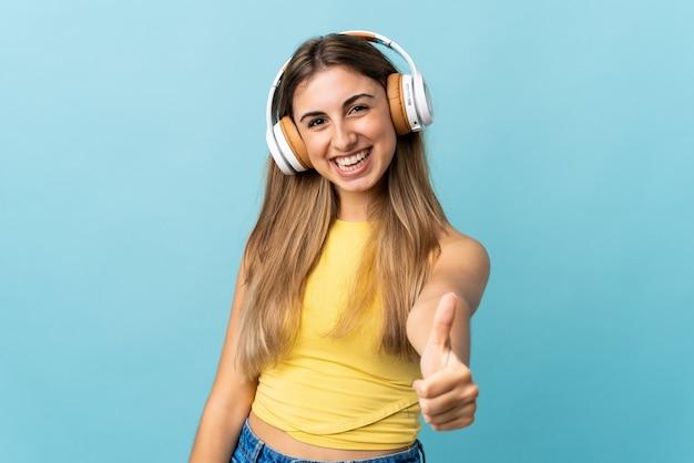 Молодая женщина на изолированном синем прослушивании музыки и с большим пальцем вверх