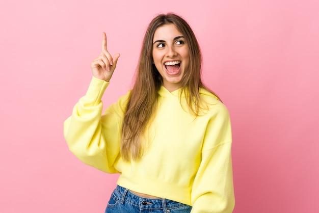 격리 된 분홍색에 젊은 여자는 손가락을 들어 올리는 동안 솔루션을 실현하려는 의도