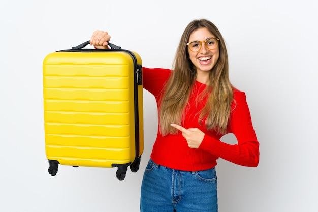 Молодая женщина на изолированном белом в отпуске с чемоданом путешествия
