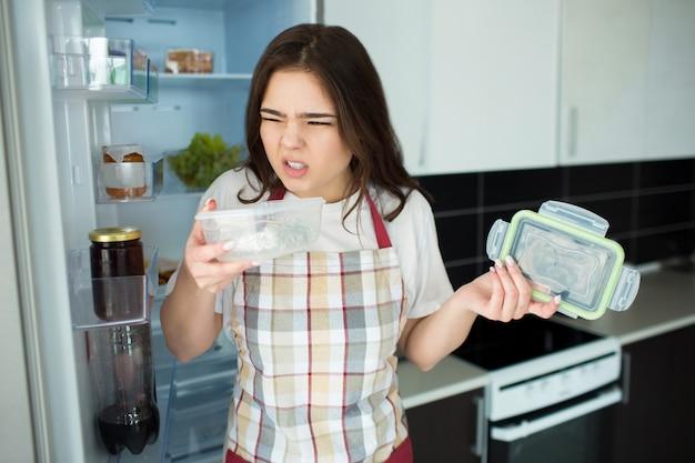 Молодая женщина на кухне. встаньте перед открытым холодильником с подносом для еды с неприятным запахом. disgution.