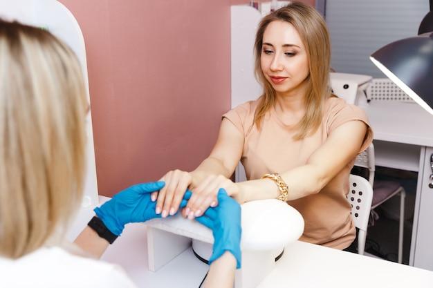 매니큐어, 미용 절차 및 개인 관리에 매니큐어 치료에 젊은 여자.