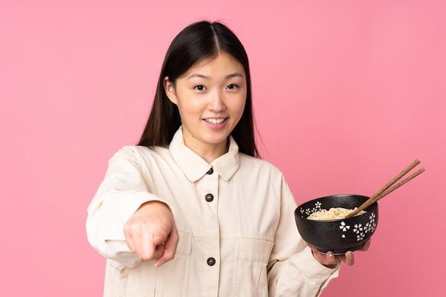 Молодая женщина на розовом указывает пальцем на тебя с уверенным выражением, держа миску лапши с палочками для еды