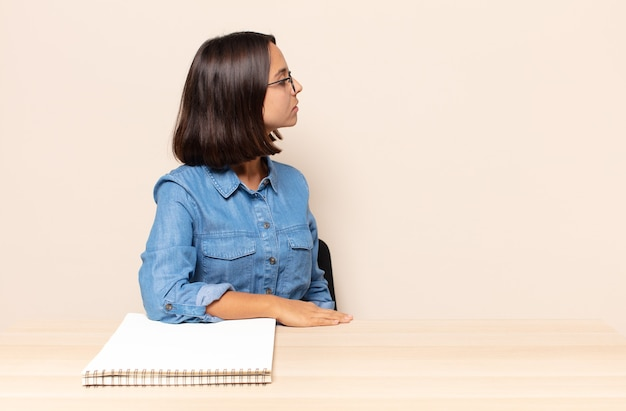 Молодая женщина на виде профиля, желающая скопировать пространство впереди, думает, воображает или мечтает