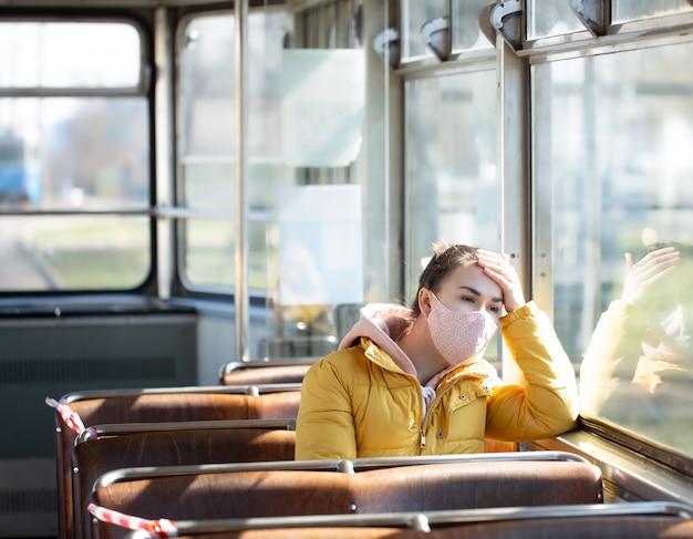 Молодая женщина на общественном транспорте во время пандемии.