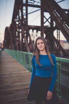 都市の夕日の肖像画として駅の若い女性