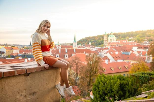 チェコ共和国プラハの旧市街の赤い屋根の背景に若い女性