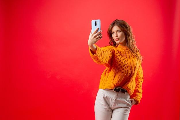 携帯電話で自分の写真を撮る赤の若い女性
