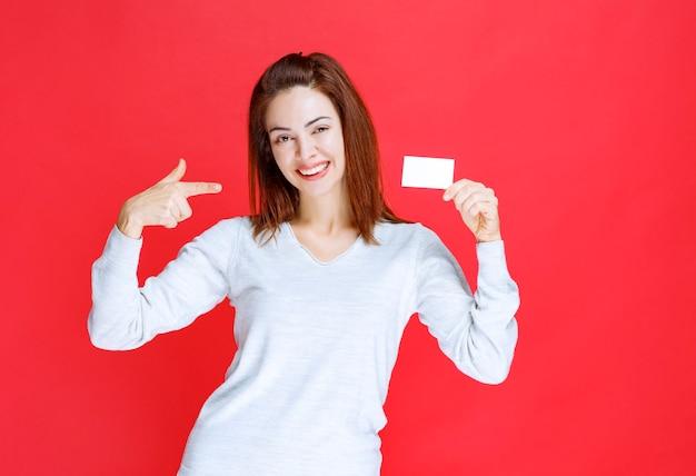 그녀의 명함을 제시 하는 빨간 벽에 젊은 여자