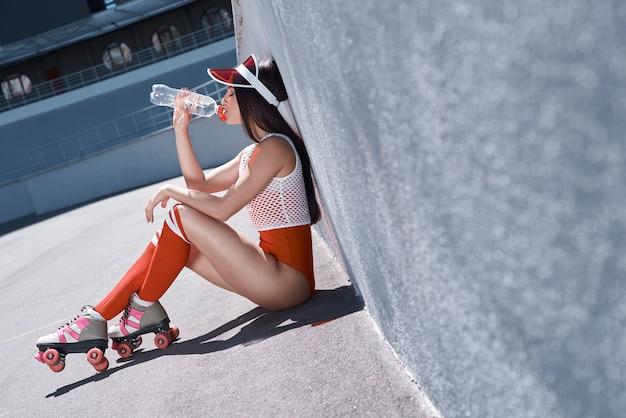 Молодая женщина на роликовых коньках и шлеме питьевой воды стильная красивая девушка в шортах и