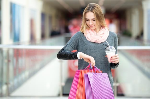 彼女の時計を見て買い物に若い女性