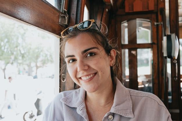 Молодая женщина в солнцезащитных очках в старом поезде в порту, улыбаясь в камеру на концепции инди-одежды, путешествий и новых впечатлений Premium Фотографии