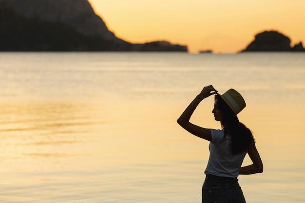 湖の岸に夕日の若い女性